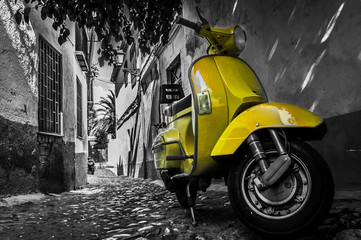 Scooter Yellow vespa scooter parked in an old empty paved street
