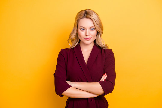 Portrait of pretty charming  woman in burgundy suit having her arms crossed looking at camera isolated on yellow background