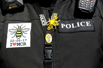 A police officer wears a badge and a bee symbol on the first anniversary of the Manchester Arena bombing, in Manchester