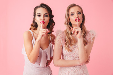 Two women in dresses having secret while showing silence gestures