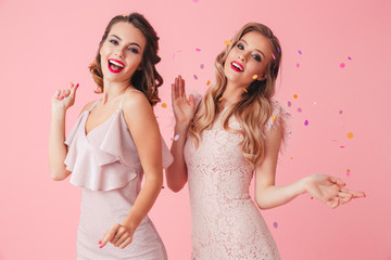 Two cheerful elegant women in dresses having fun together