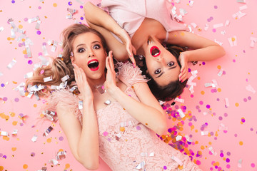 Image of excited women in dresses lying on the floor under falling colorful confetti at luxury party or carnival, isolated over pink background