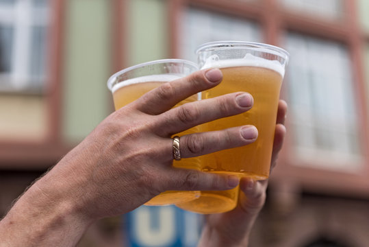 two hands and three full plastic cups with beer