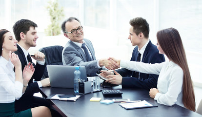 Manager and client shaking hands after discussing the contract