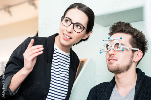 9d06ae5b53 Man with optician at eyesight test for glasses in optician shop ...