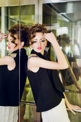 Close up fashion portrait of beautiful curly woman with red lips wearing black blouse standing in the modern elevator and posing at the camera