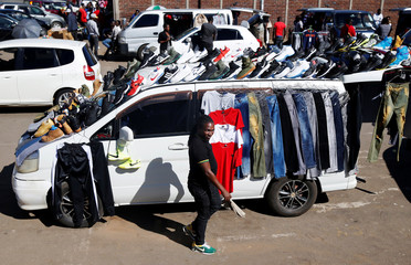 A hawker walks past his clothing stall along a street in Harare