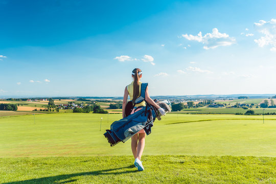 Full length rear view of an active woman carrying a blue stand bag, while walking on the grass towards a training area for professional golf in a sunny day