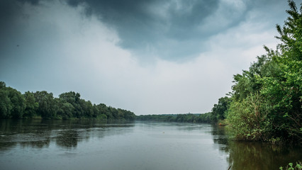 Rain and dramatic clouds over river and forest, panoramia