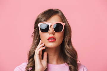 Photo closeup of sexual charming woman 20s with long curly hairstyle wearing trendy sunglasses looking at camera with fashion look, isolated over pink background