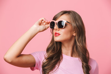 Photo closeup of gorgeous woman 20s wearing fashionable stylish sunglasses looking aside at copyspace, isolated over pink background