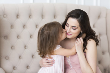 Young happy woman embrace with small daughter