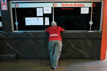 A man stands in a counter at a bus station in Caracas