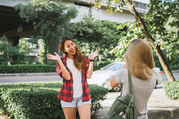 Happy beautiful traveler asian friend women carry backpack. Young joyful friend asian women using camera to making photo during city tour, cheerful emotions. Women lifestyle outdoor in city concept.