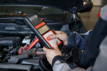 Battery charger and car in auto repair shop.
