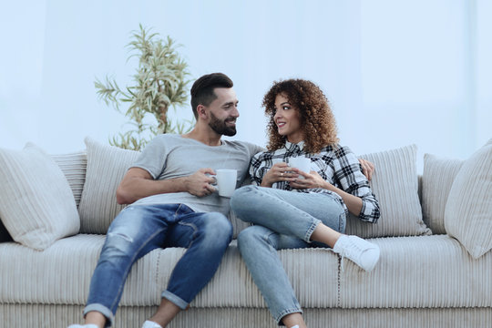 Beautiful couple holding a cup of drink while sitting on the couch at home