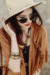 beautiful stylish boho woman in sunglasses and hat, fringe poncho and leather bag. hipster girl in gypsy look young traveler posing near river beach in mountains. sensual look.