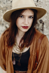 beautiful stylish hipster woman in hat portrait, sensual look. boho traveler girl in gypsy look, near beach in mountains. summer travel. atmospheric moment
