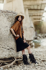 beautiful stylish boho woman with hat, fringe poncho and boots. girl in gypsy hippie look young traveler posing near river rocks in mountains. sensual look. atmospheric moment. space for text