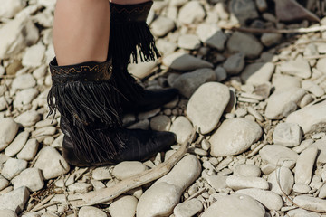 fringe boot. stylish hipster boho traveler woman wearing suede boots on river beach. gypsy girl look. wanderlust summer travel. atmospheric moment. space for text.
