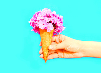 Hand holding ice cream cone with flowers
