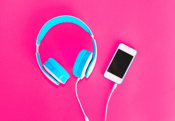 Headphones and  smartphone on a pink background