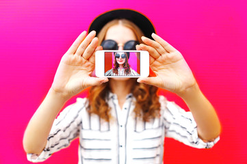 Girll taking picture self portrait on smartphone over colorful pink background