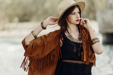 stylish hipster woman posing in hat with windy hair, in fringe poncho and accessory. boho traveler girl in gypsy look. summer travel. atmospheric moment. space for text. sensual portrait