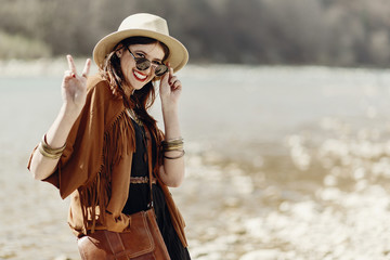 stylish hipster boho woman smiling showing peace sign in sunglasses with hat, leather bag, fringe poncho and accessory. happy traveler girl look, wanderlust summer travel. space for text
