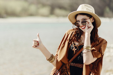 stylish hipster boho woman smiling showing thumb up, in sunglasses with hat, leather bag, fringe poncho and accessory. happy traveler girl look, wanderlust summer travel. space for text.