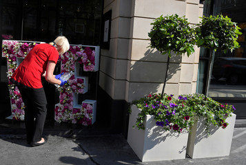 A woman uses a bottle to water a display outside of a hotel which is participating in the Chelsea In Bloom festival in London, Britain