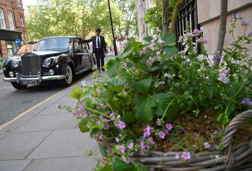 A chauffeur waits by his car next to a floral display outside of a business taking part in the Chelsea In Bloom festival in London, Britain