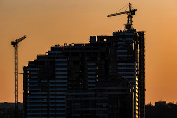 Silhouette of construction crane and new building