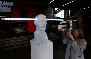 "A woman takes a photo of Russian artist Vasily Slonov's artwork called ""Bright Ideas. Lenin"" made of sculpture to Soviet state founder Vladimir Lenin and a LED light tube in Krasnoyarsk"