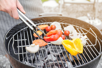 Man cooking juicy vegetables on barbecue grill