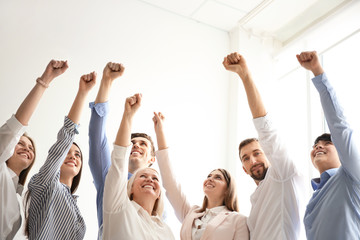 People raising fists together indoors. Unity concept