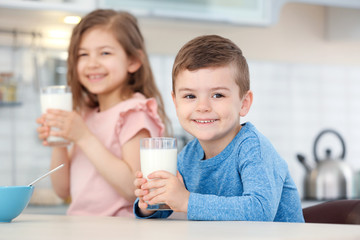 Cute little kids drinking milk in kitchen