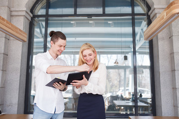 Teamwork - cute young woman manager holding tablet and talking about financial risks to a young accountant against the backdrop of large window in spacious office.