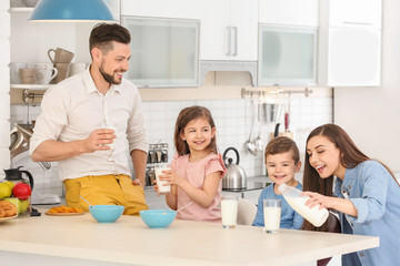 Happy family having breakfast with milk in kitchen