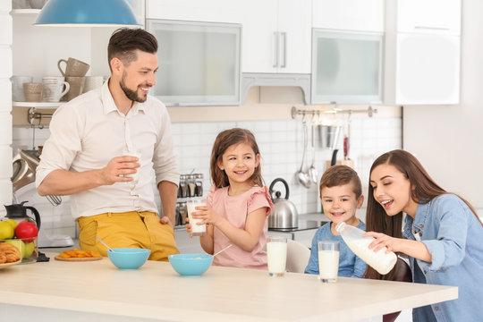Happy family having breakfast with milk in kitchen