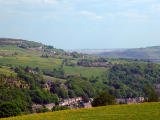 the town of hebden bridge visible at the bottom of the calder valley with surrounding pennine yorkshire countryside with fields woodland and hills in spring sunlight with bright blue sky