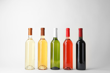 Bottles of expensive wines on light background