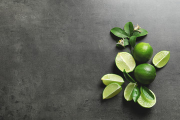 Composition with fresh ripe limes on gray background, top view