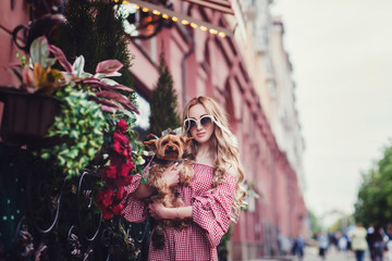beautiful young woman with her dog standing on city background