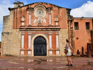 Tourist standing in front of the facade of the Convento de la Orden de los Predicadores in Santo Domingo