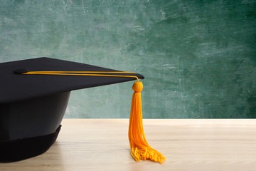 Graduated cap placed on a wooden desk in the classroom.