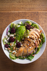 Kiwi, avocado, blackberry, spinach, walnuts salad with chicken and feta cheese. Healthy diet food bowl. overhead, vertical