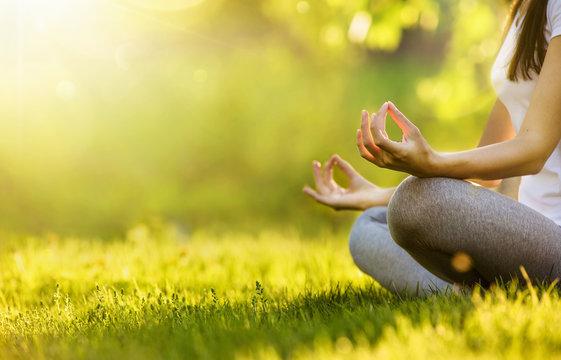 Yoga woman meditating at sunset. Female model meditating in serene harmony
