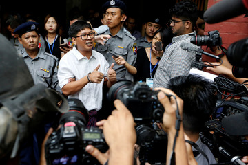 Detained and handcuffed Reuters journalist Wa Lone speaks to media after a court hearing in Yangon