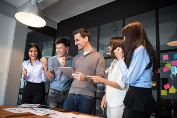 Group of young modern people in casual wear planning business strategy. Business team analyzing income charts and graphs. Setup studio shooting.